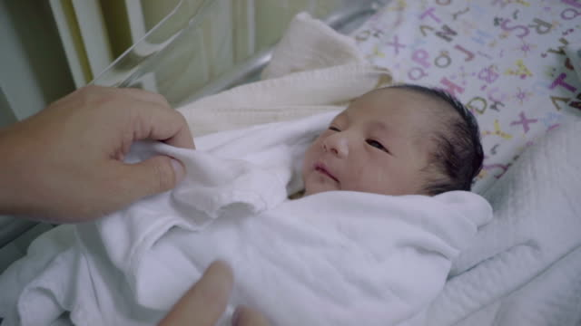 Mother wraping blanket a baby. video
