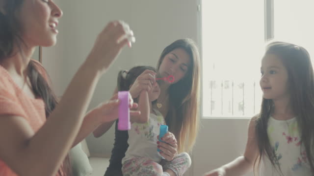 Mothers and daughters having fun blowing bubbles video
