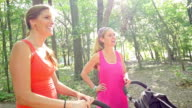 Mothers talking after exercising in park with jogging strollers video