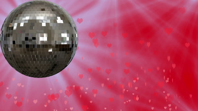 Motion graphic of revolving mirror ball with hearts background video