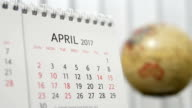 Motion of April 2017 calendar with blur earth globe turning background video