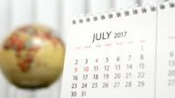 Motion of July 2017 calendar with blur earth globe turning background video