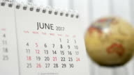 Motion of June 2017 calendar with blur earth globe turning background video