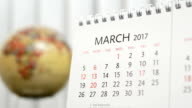 Motion of March 2017 calendar with blur earth globe turning background video