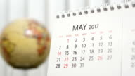 Motion of May 2017 calendar with blur earth globe turning background video
