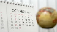 Motion of October 2017 calendar with blur earth globe turning background video