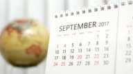 Motion of September 2017 calendar with blur earth globe turning background video