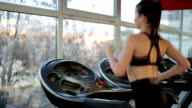 Motivated woman training in the gym, running on treadmill, active video