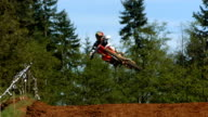 Motocross racer soaring over jump, super slow motion video