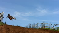 Motocross racers fly over jump, slow motion video