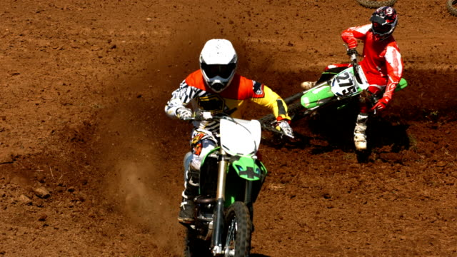 Motocross racers on dirt track, super slow motion video