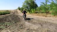 Motocross rider on his enduro bike riding away kicking up dust video