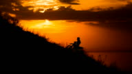 motocross rider storms obstacle. Climb up the hill on the road. Sunset painted the sky video