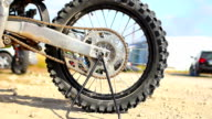 Motocross wheel and tire pan and slide on swingarm at daytime. video