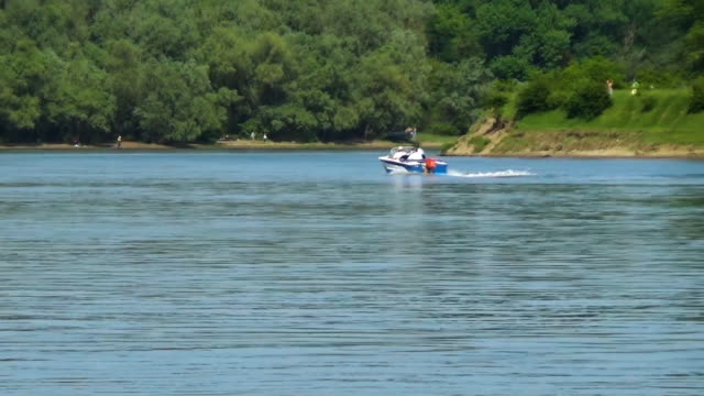 A motor boat with three passengers sails along the river bank video