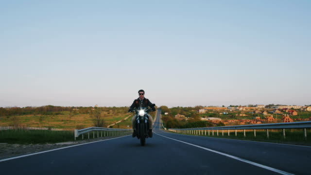 motorbike on the road riding. having fun driving the empty road on a motorcycle tour journey. copyspace for your individual text. video