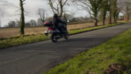 Motorcycle glides past in slow motion away from camera video