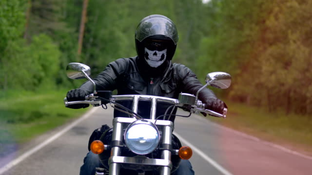 A motorcyclist, biker on a lonely road drives wearing a skull mask. 4K. video