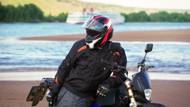 Motorcyclist resting on the river bank next to his motorcycle video