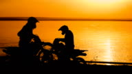 Motorcyclist silhouette at sunset. He freely travels around the sands on the shore of the river video