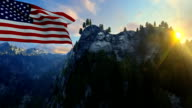 Mount Rushmore with USA Flag blowing in the wind against blue sky video