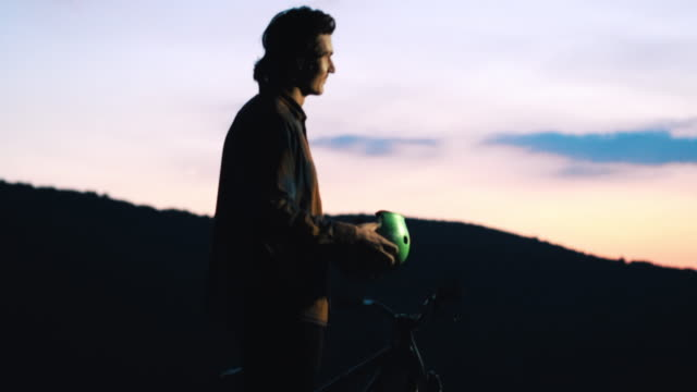 Mountain bike cyclist putting on his cycling helmet and starts riding at sunset. video
