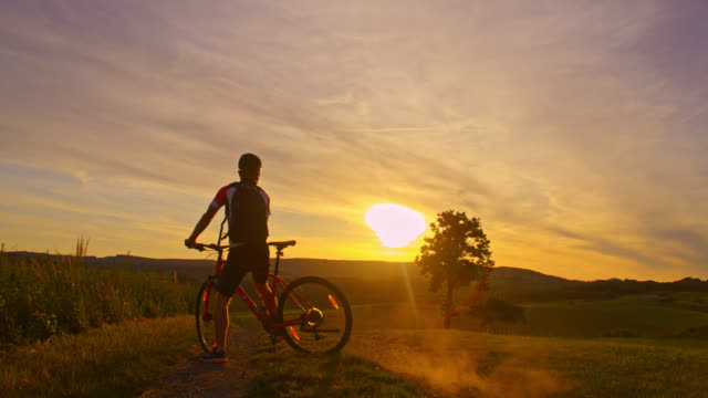 SLO MO Mountain biker cycling uphill at sunset video