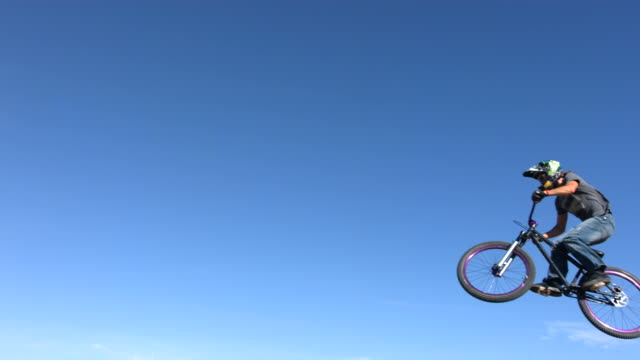 Mountain biker flies through air, slow motion video