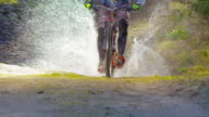 SLO MO Mountain biker going down trail and into puddle video