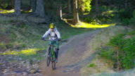 Mountain biker going through a puddle on forest trail video