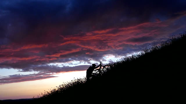Mountain biker moving up at sunset-slow motion video