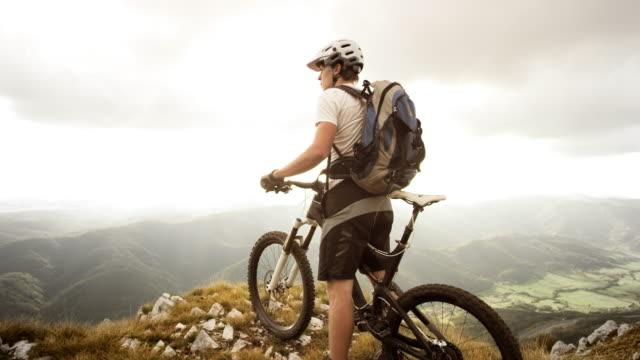 TU SLO MO mountain biker on the top of mountain video