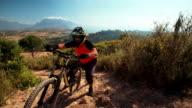 Mountain biker pushing his bike over rough terrain video