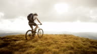 SLO MO mountain biker reaching the top and raising hands video