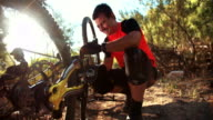 Mountain biker repairing his bike on a trail video