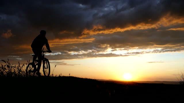 Mountain biker riding at sunset-slow motion video