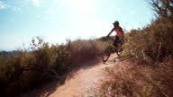 Mountain biker riding downhill on a cross country dirt path video