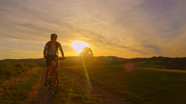 SLO MO Mountain biker riding his bike uphill at sunset video