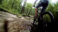 Mountain biker riding through a dirty puddle video