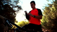 Mountain biker sitting on bike looking at his smart phone video