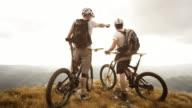 SLO MO mountain bikers admiring nature at edge of plateau video