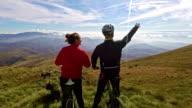 Mountain bikers enjoying a view from the ridge 4K video
