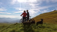 Mountain bikers with dogs 4K video