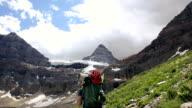 Mountain climber walks along mountain trail towards towering peak video