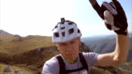 Mountain cyclist making funny selfies on the mountain top video