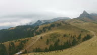 Mountain landscape in autumn with peaks in the background and low pressure atmospheric front causing dense layer of clouds and mist over the valleys, aerial view video