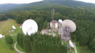 Mountain location with big satellite antennas array and communications tower , electronic equipment for signal broadcasting , aerial view video