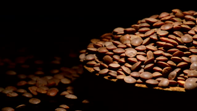 Mountain of lentils legume on a plate gyrating on black background video
