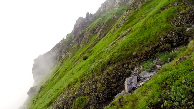 Mountain side in the cloud. Hikers video