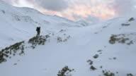 AERIAL Mountaineer walking on snow capped ridge video